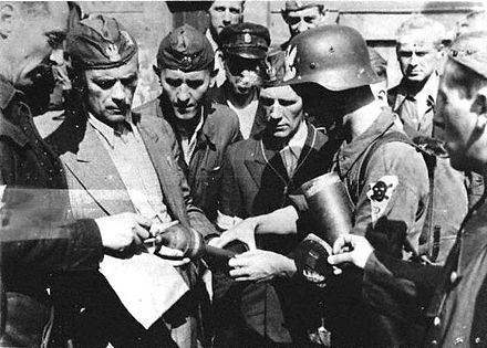 "Cyprian Odorkiewicz commander of ""Krybar"" Regiment (second from left) inspects ammunition for PIAT anti-tank weapon belonging to ""Rafalki"" unit during Warsaw Uprising 1944 Warsaw Uprising - Cyprian Odorkiewicz and Rafalki.jpg"
