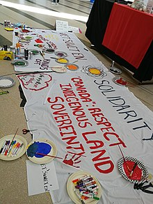 "Image of banner created by participants of a Wet'suwet'en Solidarity event at Vari Hall, March 11, 2020. The banner is painted with the phrases ""Wet'suwet'en Solidarity"", ""stand strong"", ""hands off"", ""no pipeline on stolen land"", "" ""Canada"": respect indigenous land sovereignty"""