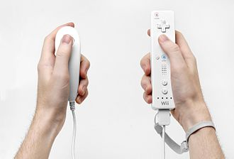 Wii - A Nunchuk, Wii Remote and strap shown in hand