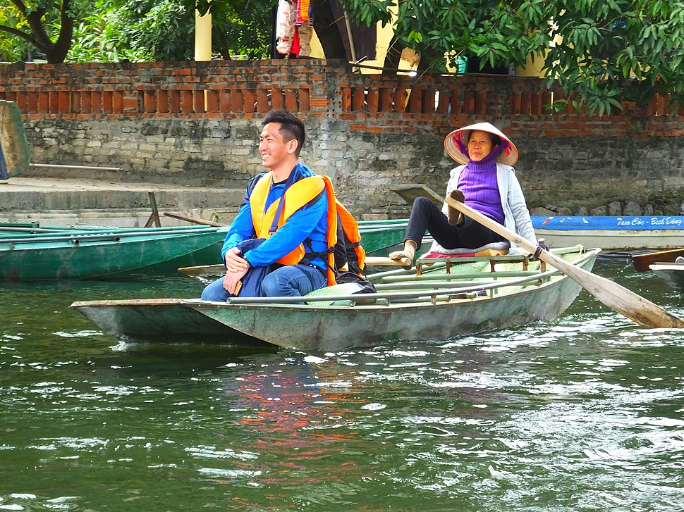 Woman rowing sampan with her feet in Ninh Bình Province of northern Vietnam