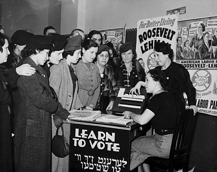 Women surrounded by posters in English and Yiddish supporting Franklin D. Roosevelt, Herbert H. Lehman, and the American Labor Party teach other women how to vote, 1936. Women voter outreach 1935 English Yiddish.jpg