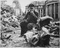 """This Nazi officer is eating his words, and a can of C-rations, in the ruins of Saarbrucken. The day we hung our... - NARA - 535981.tif"