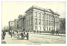 A depiction of the Courthouse showing carts on the street and people walking on the sidewalks