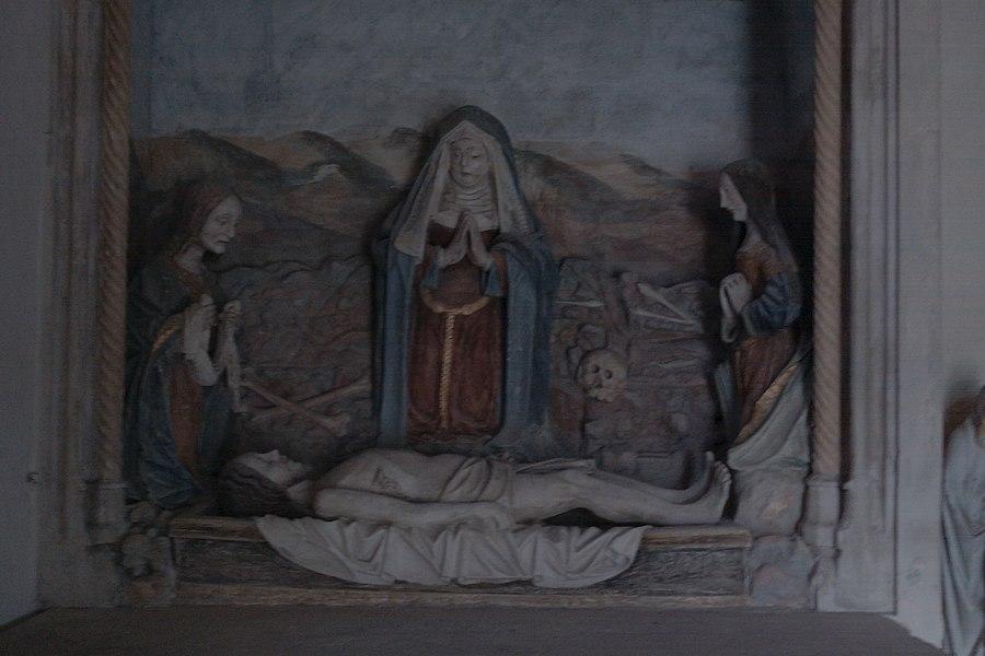 La Mise au tombeau - groupe sculpté en pierre calcaire din XVIe  Le christ allongé sur le tombeau St Jean à gauche tenant un ling Ste Madeleine en prière La vierge au centre Dérrière, rocher,crâne,tibias entrecroisées