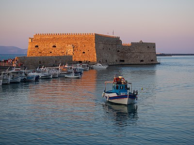 A fishing boat entering the port of the Heraklion, with the 16th century Venetian fortress Koules