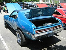 "shows the rear end of a 1972 Javelin finished in blue with the tail lamp design following the ""egg crate"" pattern"