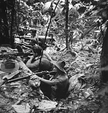 Soldiers in slouch hats occupy a defensive position in a jungle clearing