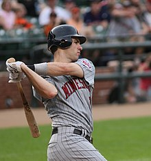 A baseball player in a pinstriped uniform follows through with a swing of a baseball bat.