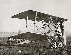 Three quarters view of military biplane on the ground with pilot in cockpit and check paint pattern on engine cowling and wheels