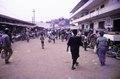 ASC Leiden - F. van der Kraaij Collection - 05 - 040 - A waterside open air market with people. To the right Choithram & Sons (Liberia), Inc - Monrovia, Waterside, Montserrado, Liberia, 1975.tif