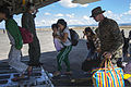 A U.S. Marine with Combat Logistics Regiment 4 with the 3rd Marine Expeditionary Brigade helps carry on personal belongings of Filipinos aboard a U.S. Marine Corps C-130 Hercules aircraft for transport to Manila 131115-M-UY543-095.jpg