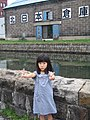 A girl in front of stoneware house in Misaki, Japan; August 2009.jpg