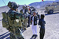 A member of Coalition Special Operations Forces, left, gives a pen to a young boy during a presence patrol in Sayed Abad district, Wardak province, Afghanistan, Nov. 6, 2011 111106-A-VT689-002.jpg