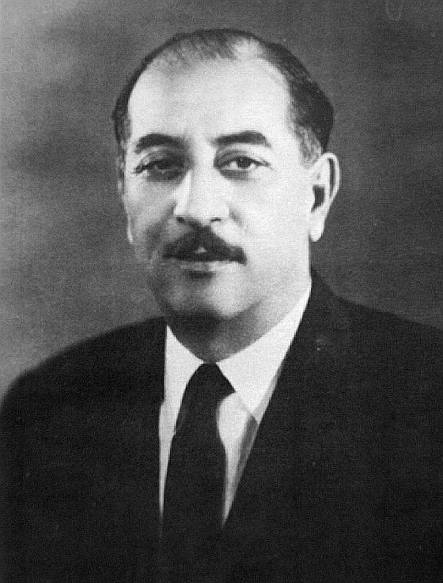Black-and-white photo of middle-aged, mustachioed man in suit