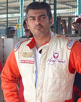 Ajith Kumar poses in a race outfit