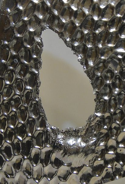 Datei:Aluminium heat reflector with hole melted through by high temperatures.jpg