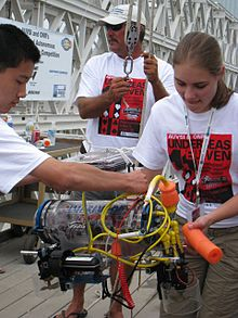 Two teenagers look down at a small vehicle. The vehicle is enclosed in a clear plastic tube and the machinery inside is clearly visible. To the right, a female student holds the vehicle. To the left, a male student adjusts tubing on the vehicle. In the back, a middle-aged man is holding a harness for the vehicle.