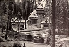 A monochrome photograph of a 75-foot-tall building with steeply pitched roof elements, seen amid tall pine trees from across a river. A rustic one-lane bridge over the river is in the foreground.