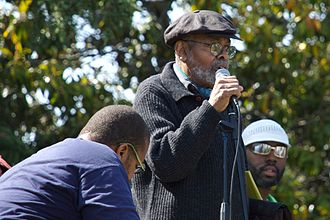 Amiri Baraka - Baraka addressing the Malcolm X Festival from the Black Dot Stage in San Antonio Park, Oakland, California, while performing with Marcel Diallo and his Electric Church Band