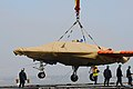 An X-47B is loaded onto flight deck of USS George H.W. Bush. (8720066597).jpg