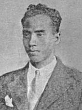 A faded image of a man with short, curly hair in a suit and tie.