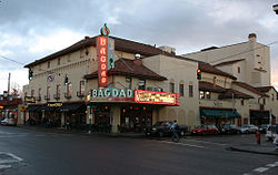 Photograph of a tile-roofed building with a large marquee on an urban street corner