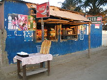Small wooden table stacked with French bread in front of a storefront kiosk in Toliara