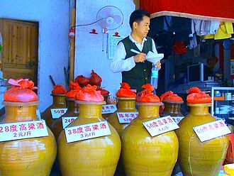 Baijiu - Crockery jars of locally-made baijiu in a liquor store in Haikou, Hainan, China, with signs indicating alcoholic content and price per jin (500 grams)