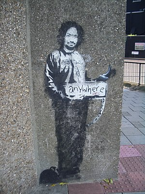 Banksy - A stencil of Charles Manson in a prison suit, hitchhiking to anywhere, Archway, London