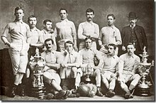 A group of men, most of whom are wearing shorts and football shirts, holding two trophies, one of which is the FA Cup