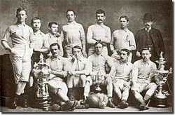 A group of twelve men, eleven in association football attire typical of the late nineteenth century and one in a suit and bowler hat.  They are displaying a number of trophies.
