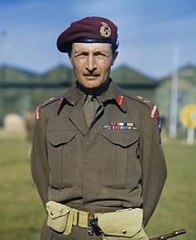 View from waist up of a man with short hair and moustache in battle dress with campaign ribbons. He is wearing a tie, airborne shoulder tabs, a maroon beret with a general's badge on it, and major-general's rank badges.