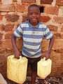 Boy carrying water in Kamokya, Kampala (4332277472).jpg