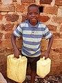 Boy carrying water in Kamokya, Kampala (4332277472).jpg
