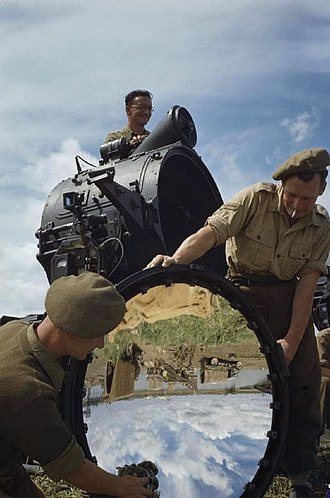 Searchlight - Members of a Royal Artillery, anti-aircraft searchlight detachment clean the mirror of their searchlight, Italy, April 1945