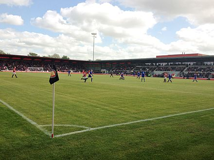 Broadhurst Park's test event between F .C. United's first team (red) and an Invitational XI (blue) Broadhurst Park - Corner.JPG