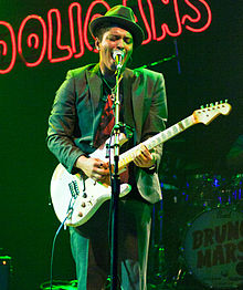 Mars, in a green suit and hat, playing guitar onstage