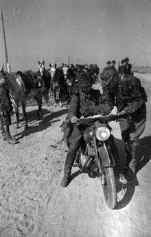 uma fotografia em preto e branco de uma equipe de motocicleta militar alemã com vários cavalos ao fundo