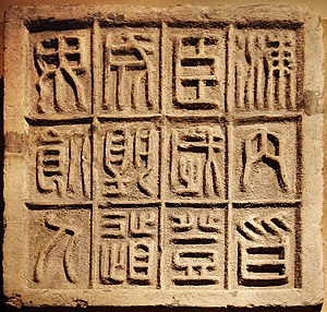 Legalism (Chinese philosophy) - Small seal scripts were standardized by Li Si after the First Emperor of China after he gained control of the country, evolving from the larger seal scripts of previous dynasties.  The 12 characters on this slab of floor brick affirm that it is an auspicious moment for the First Emperor to ascend the throne, as the country is united and no men will be dying along the road.