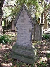 An elegant sandstone gravestone with a gabled top, standing in dappled light under trees
