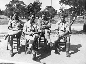 Fred Baker (soldier) - Baker, a captain at the time, sitting (3rd left) with other members of the 28th Battalion
