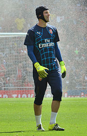 A colour photograph of Petr Čech, warming up in Arsenal training gear.