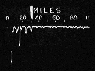 """Radar display - Chain Home is the canonical A-scope system. This image shows several target """"blips"""" at ranges between 15 and 30 miles from the station. The large blip on the far left is the leftover signal from the radar's own transmitter; targets in this area could not be seen. The signal is inverted to make measurement simpler."""