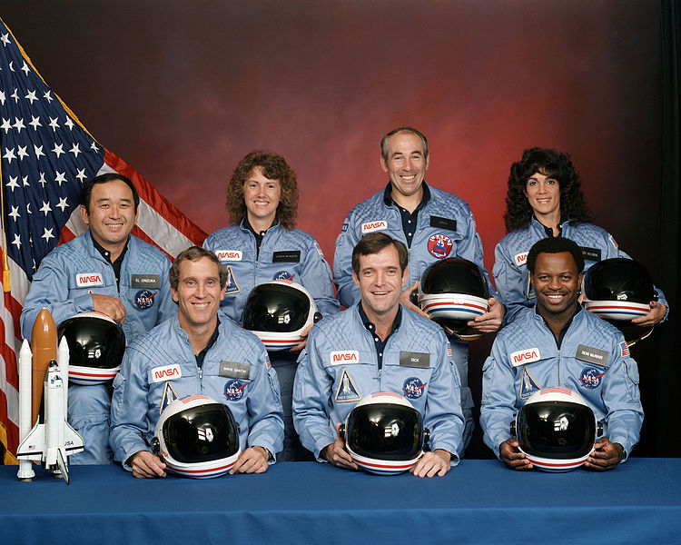 The crew of Space Shuttle mission STS-51-L pose for their official portrait on November 15, 1985. In the back row from left to right: Ellison S. Onizuka, Sharon Christa McAuliffe, Greg Jarvis, and Judy Resnik. In the front row from left to right: Michael J. Smith, Dick Scobee, and Ron McNair.