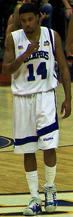 Chris Douglas-Roberts is walking during a college basketball game while wearing the white Memphis University uniform. He is holding a mouthguard and his white socks are almost up to his knees.