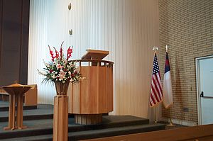 Freedom of religion in the United States - A Christian flag displayed alongside the flag of the USA next to the pulpit in a church in California. Note the eagle and cross finials on the flag poles.