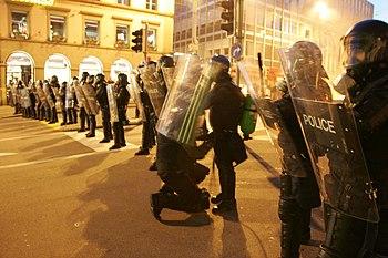 English: Policeman in riot control gear checki...