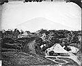 Collectie NMvWereldculturen, TM-60035214, Foto- 'Gezicht op een landweg waaraan twee gebouwen gelegen zijn, waarvan één de societiet', fotograaf onbekend, 1900-1925.jpg