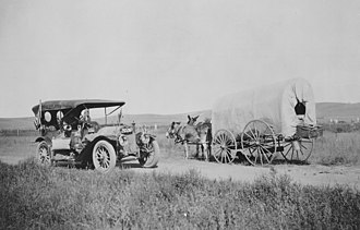 A. L. Westgard - Covered wagon with jackrabbit mules encounters an automobile on the trail near Big Springs, Nebraska by A. L. Westgard, 1912