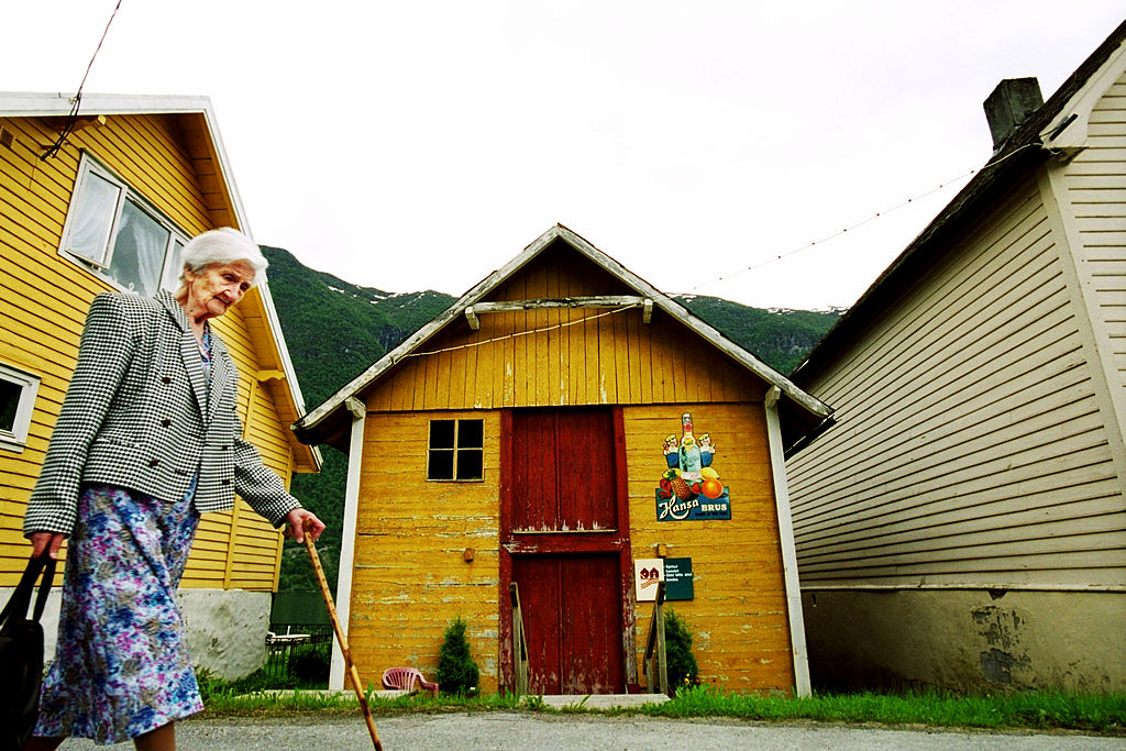 An elderly woman walks past a colorful building.